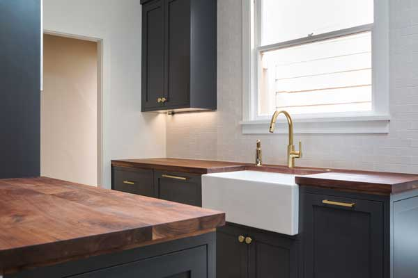 The Look Was Completed By Installing Dark Blue Kitchen Cabinetry Modern Appliances Walnut Countertops And Brass Accents